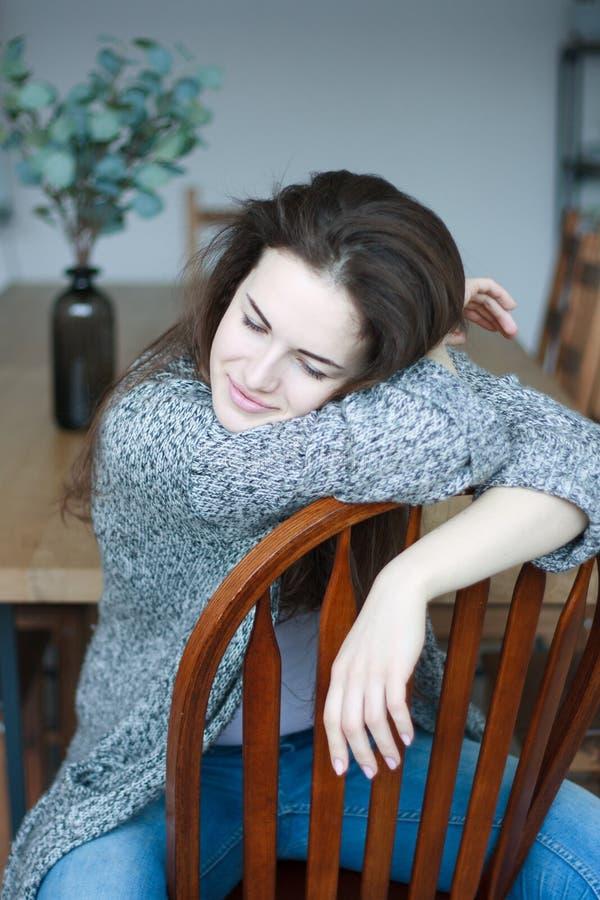 Bella giovane donna castana che si siede sulla sedia di legno fotografia stock