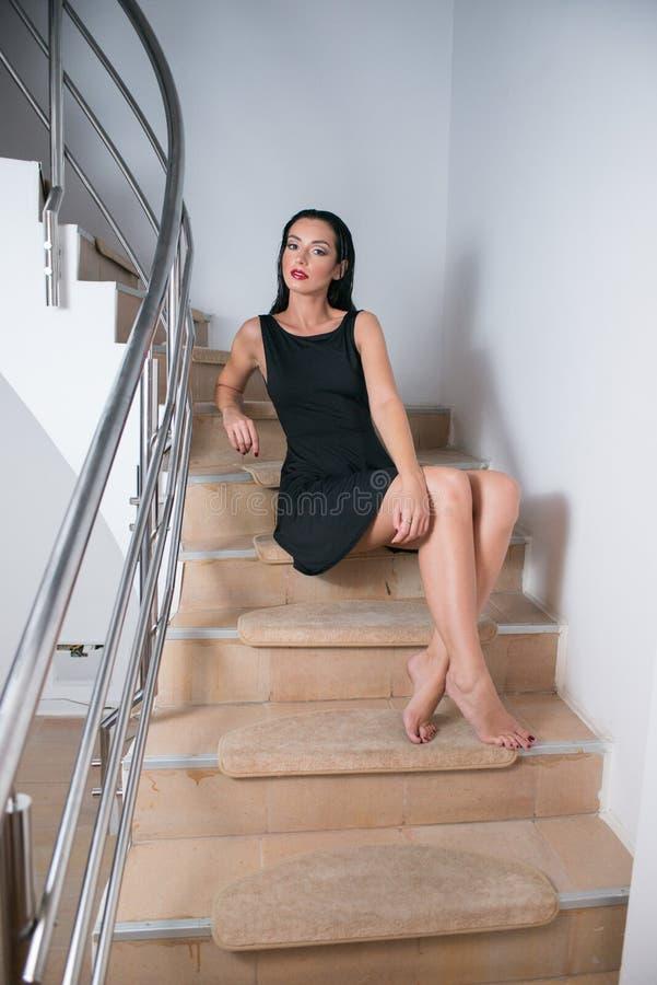 Bella giovane donna castana che si siede sulle scale nel nero immagini stock