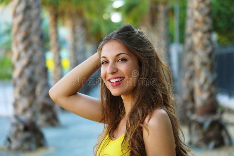 Bella giovane donna castana che sorride con il sorriso perfetto in un parco che aspetta qualcuno immagini stock libere da diritti