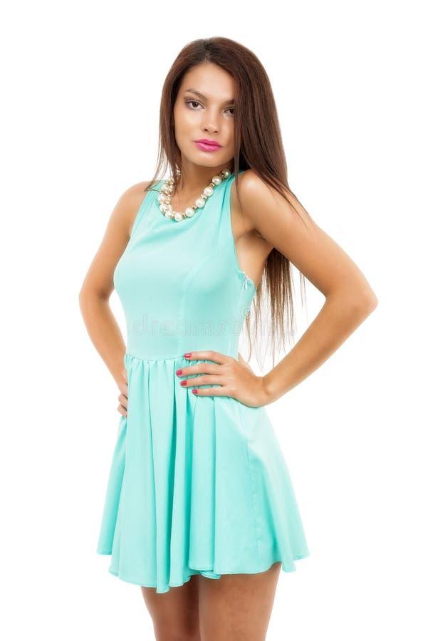 Bella giovane donna castana esile che indossa un isolato blu del vestito fotografie stock