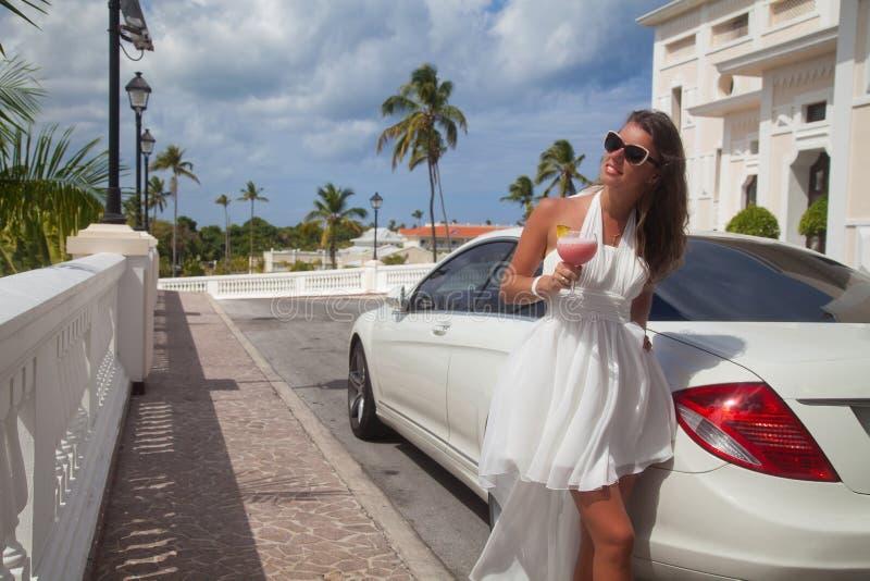 Bella giovane donna castana in vestito bianco vicino all'automobile. immagine stock libera da diritti