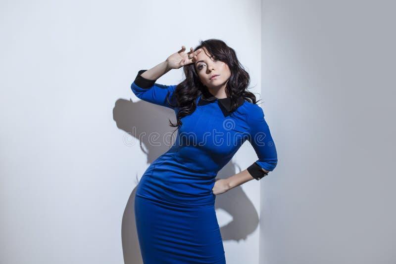 Bella giovane donna castana in vestito blu contro un bianco wal fotografia stock