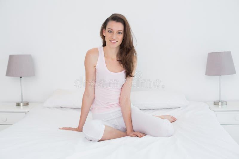 Bella giovane donna casuale che si siede a letto immagini stock libere da diritti