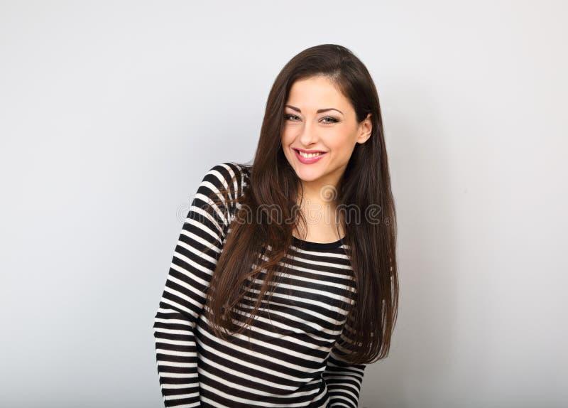 Bella giovane donna casuale sorridente nel cardigan a strisce di modo sul fondo blu di colore Stile di capelli lungo immagine stock libera da diritti