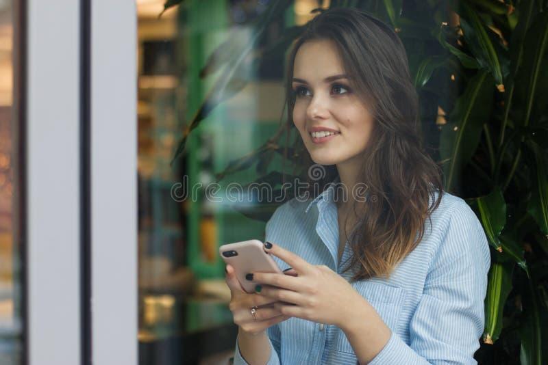 Bella giovane donna caucasica sveglia nel caffè, facendo uso del telefono cellulare e della condizione vicino a sorridere della f fotografia stock