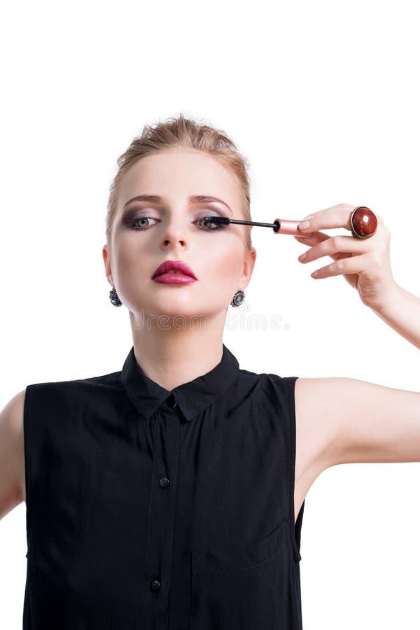 Bella giovane donna che applica mascara con la spazzola, ritratto di bellezza dello studio Applicazione del cosmetico, trucco deg immagine stock libera da diritti