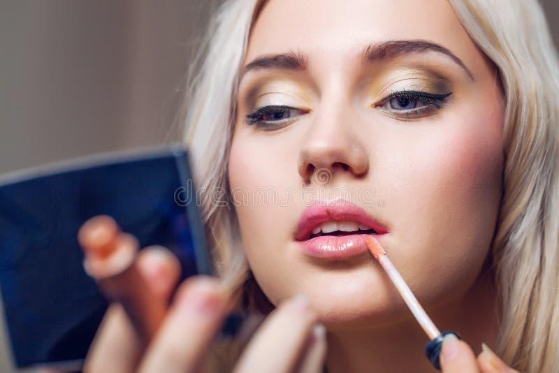 Bella giovane donna che applica trucco delle labbra con la spazzola cosmetica fotografia stock libera da diritti