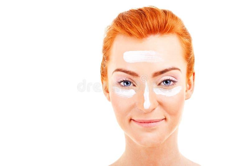 Bella giovane donna che applica una crema sul suo fronte immagini stock libere da diritti