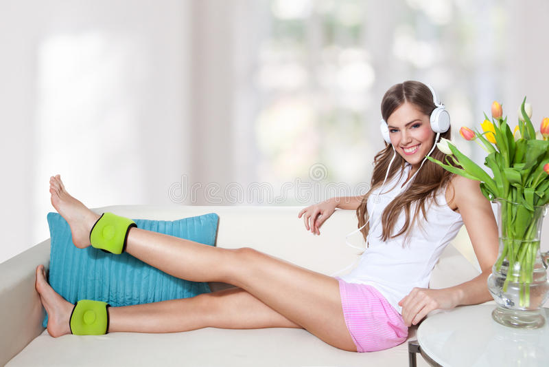 Bella giovane donna che ascolta la musica mentre facendo i exercis della gamba fotografie stock libere da diritti