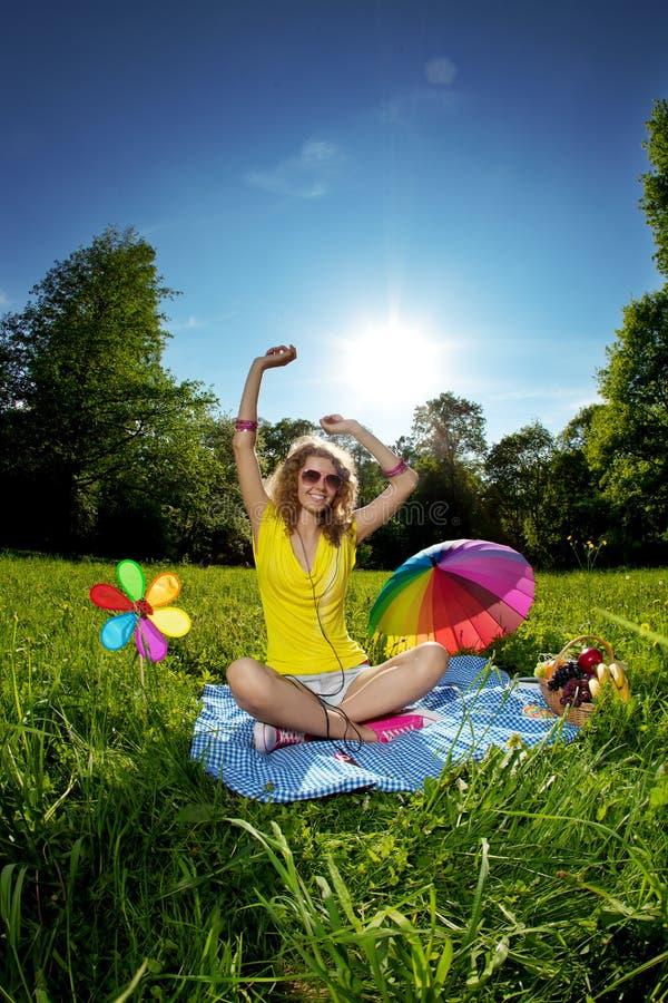 Bella giovane donna che ascolta la musica nel parco fotografie stock