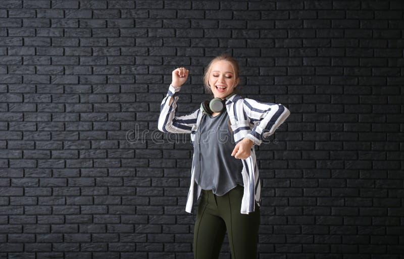 Bella giovane donna che balla contro il muro di mattoni scuro fotografie stock libere da diritti