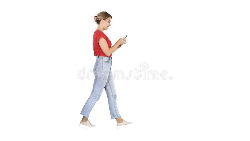 Bella giovane donna che cammina e che legge messaggio di testo sul suo telefono cellulare su fondo bianco fotografia stock libera da diritti