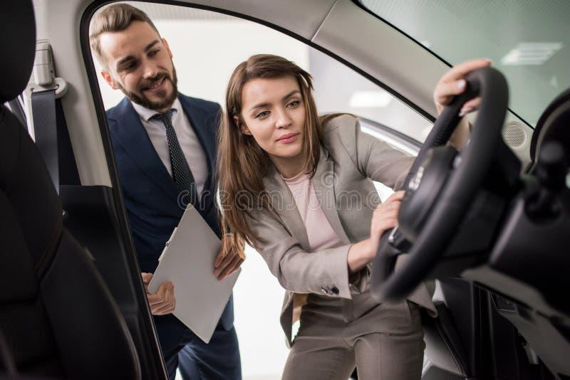 Bella giovane donna che compra nuova automobile immagini stock