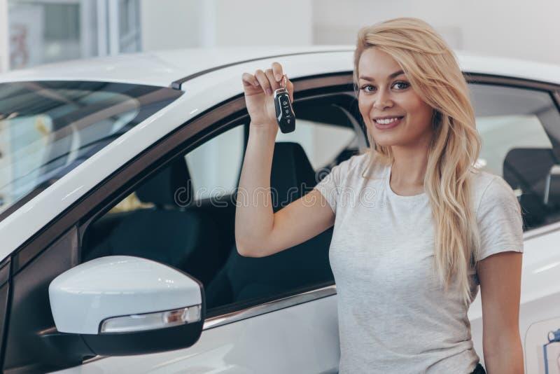 Bella giovane donna che compra nuova automobile alla gestione commerciale fotografia stock