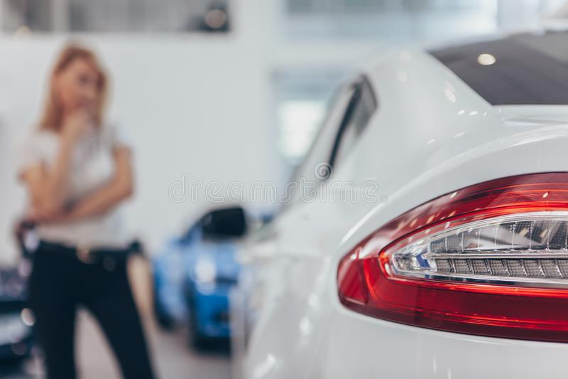 Bella giovane donna che compra nuova automobile alla gestione commerciale fotografie stock libere da diritti