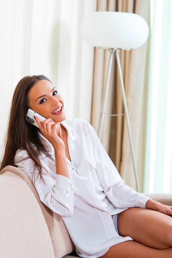 Bella giovane donna che comunica sul telefono immagini stock