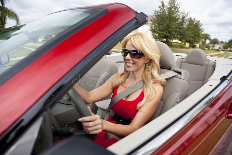 Bella giovane donna che conduce automobile convertibile immagine stock