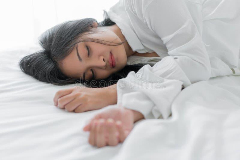 Bella giovane donna che dorme sul letto alla camera da letto fotografie stock libere da diritti