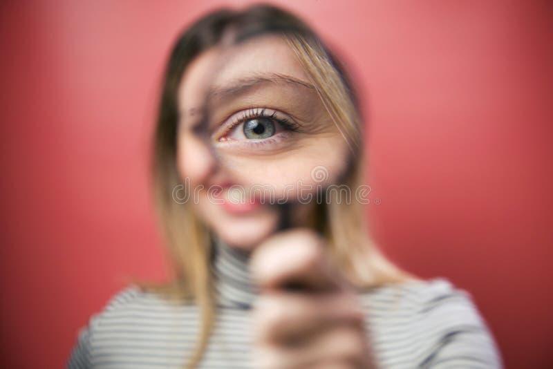 Bella giovane donna che esamina tramite la lente d'ingrandimento la macchina fotografica sopra fondo rosa fotografia stock