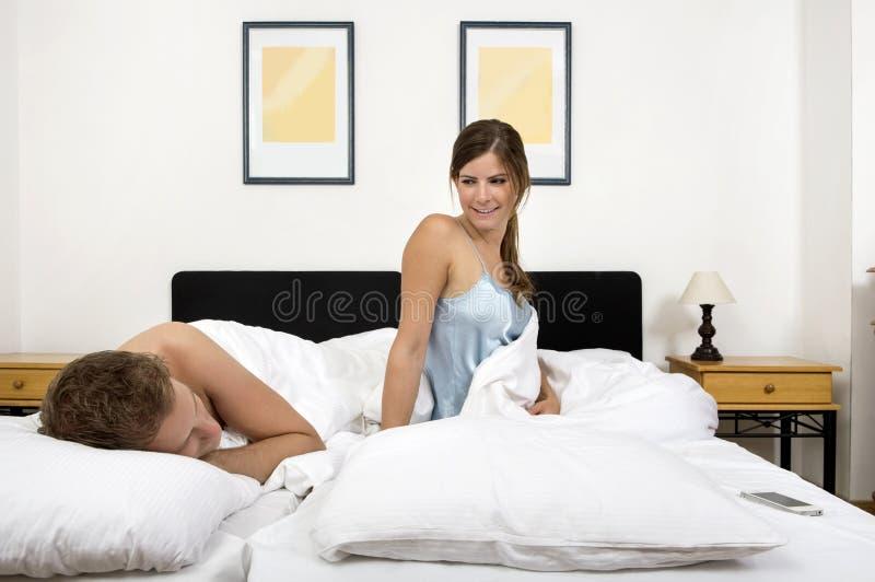 Bella giovane donna che esamina uomo che si trova a letto a casa immagini stock