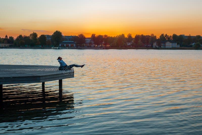 Bella giovane donna che excercising su una piattaforma fuori all'acqua immagine stock libera da diritti