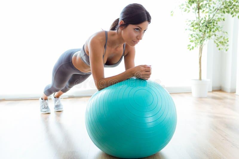 Bella giovane donna che fa esercizio di pilate con la palla di forma fisica a casa immagine stock