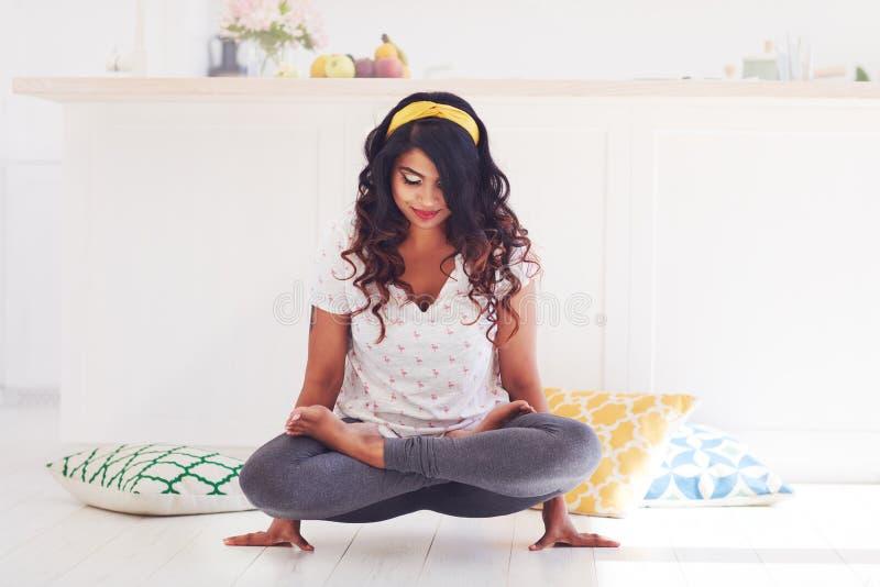 Bella giovane donna che fa posa del galletto di yoga di Kukkutasana a casa fotografia stock