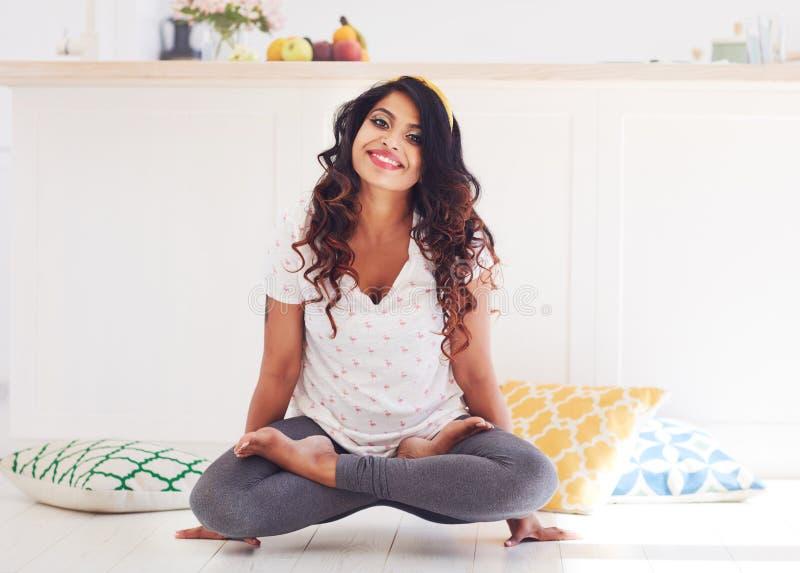 Bella giovane donna che fa posa del galletto di yoga di Kukkutasana a casa immagine stock