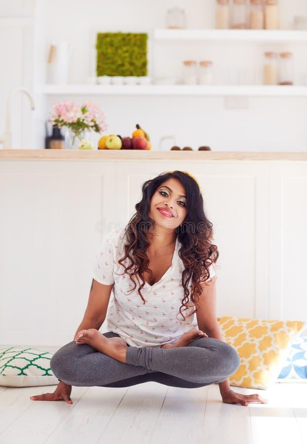 Bella giovane donna che fa posa del galletto di yoga di Kukkutasana a casa fotografie stock