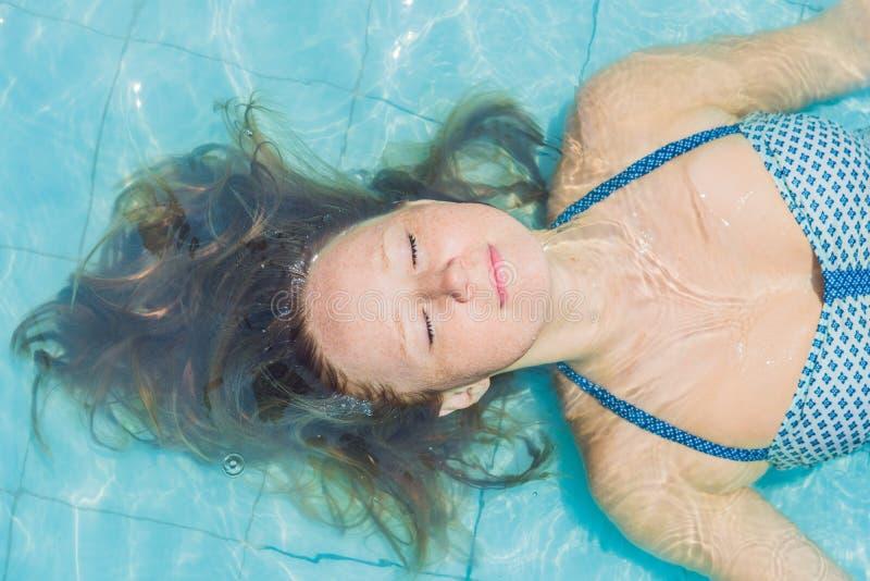 Bella giovane donna che galleggia nello stagno che si rilassa vista superiore Concetto di festa fotografie stock