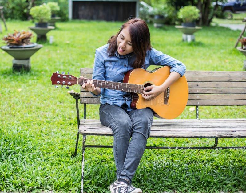 Bella giovane donna che gioca chitarra che si siede sul banco, concetto felice di tempo immagine stock