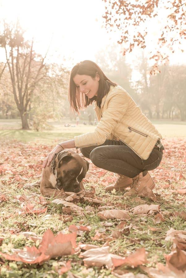 Bella giovane donna che gioca con il suo cane nella foresta immagini stock libere da diritti