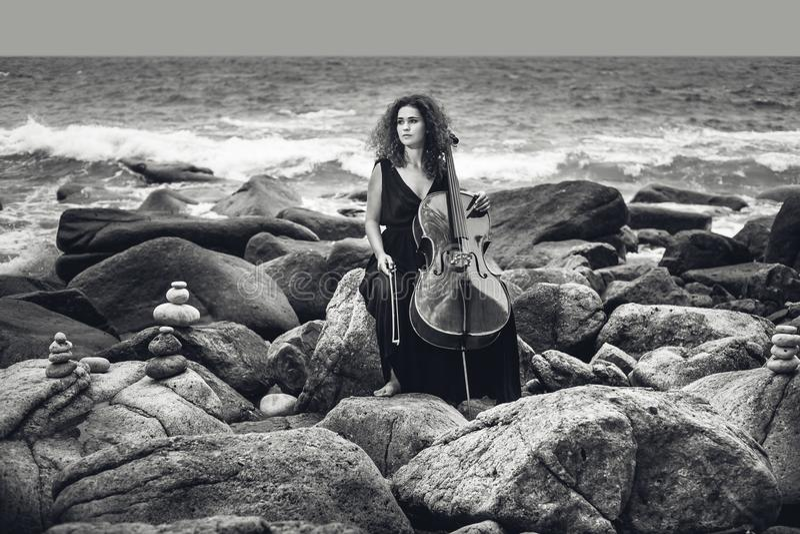 Bella giovane donna che gioca violoncello sulla spiaggia di pietra al wea tempestoso fotografie stock