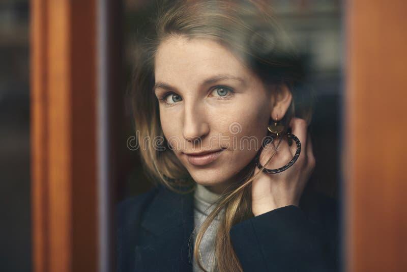 Bella giovane donna che guarda attraverso il vetro di una porta immagine stock