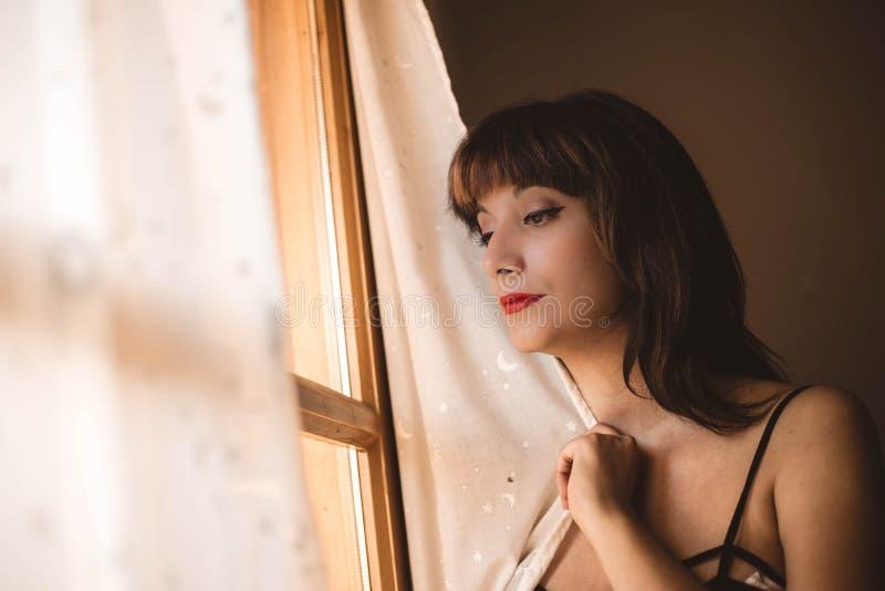 Bella giovane donna che guarda fuori la finestra che aspetta qualcuno immagine stock