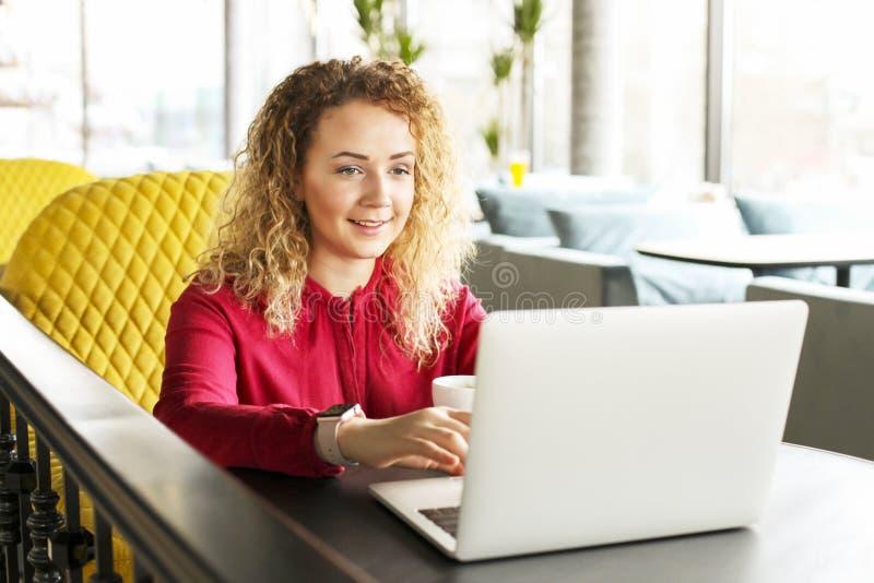 Bella giovane donna che lavora a distanza sul suo computer portatile alla moda alla caffetteria dei pantaloni a vita bassa Free l fotografia stock