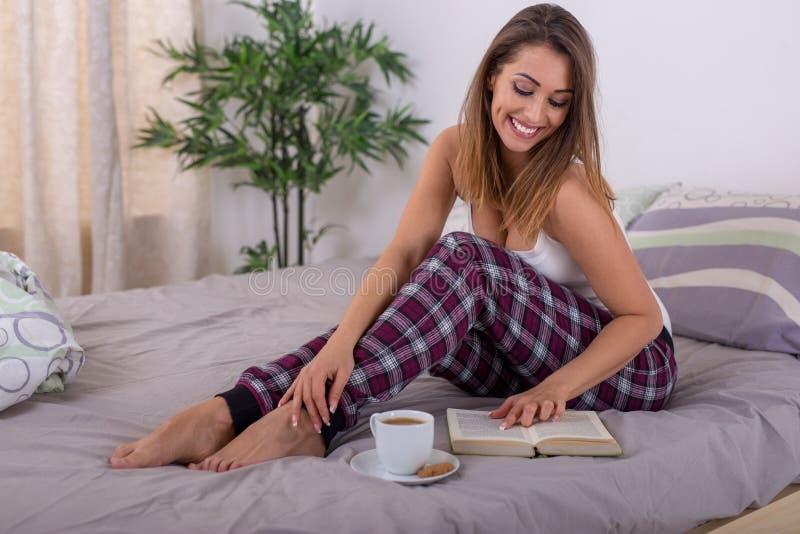 Bella giovane donna che legge un libro a letto con caffè immagine stock libera da diritti