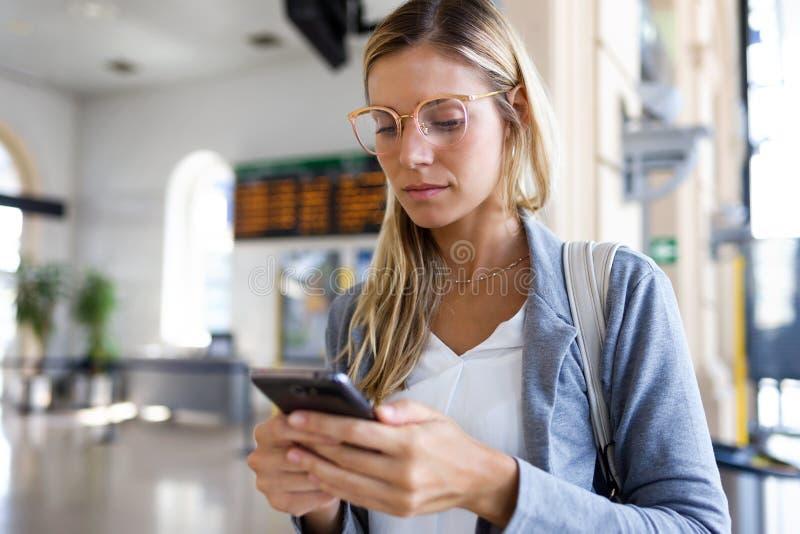 Bella giovane donna che manda un sms con il suo telefono cellulare nel corridoio di stazione ferroviaria fotografie stock