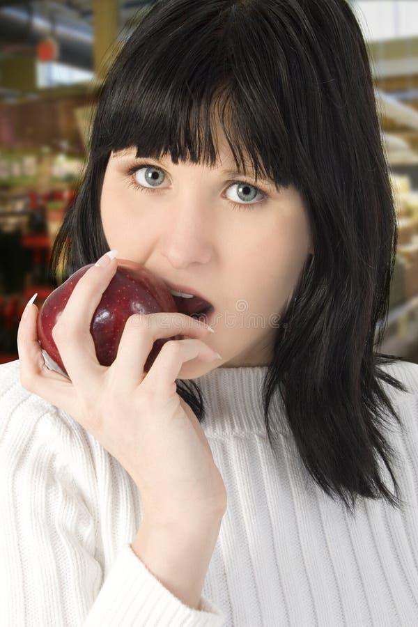 Bella giovane donna che mangia Apple fotografia stock libera da diritti