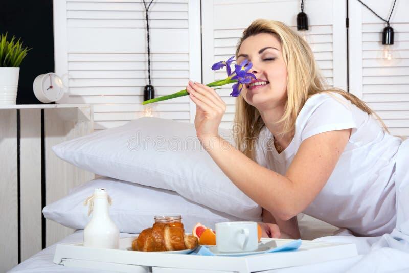 Bella giovane donna che mangia prima colazione a letto Sorpresa dal marito caro Celebrazione del giorno di una donna, festa della fotografie stock libere da diritti