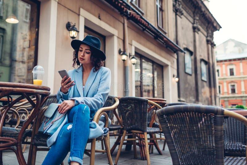 Bella giovane donna che mangia succo d'arancia in caff? all'aperto mentre per mezzo dello smartphone immagine stock