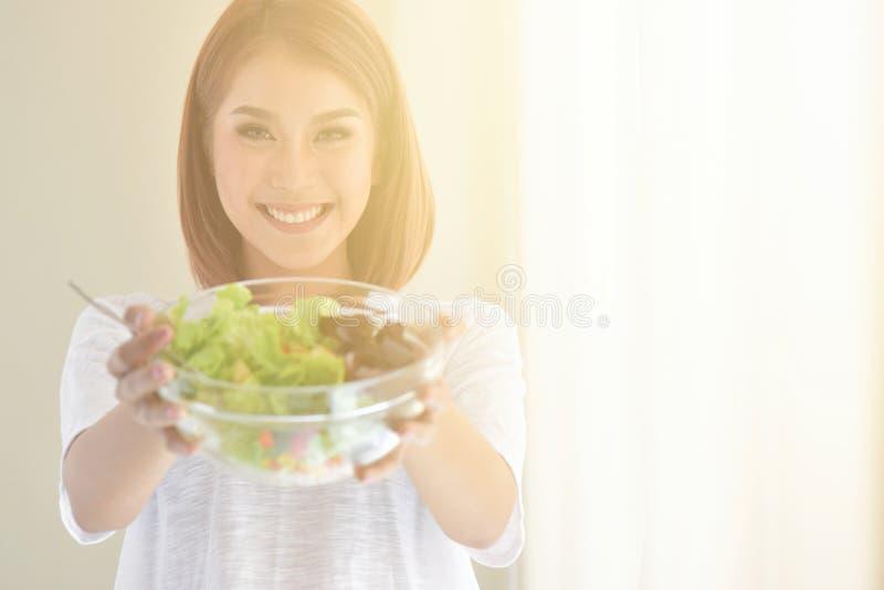 Bella giovane donna che mangia una ciotola di insalata organica sana immagini stock