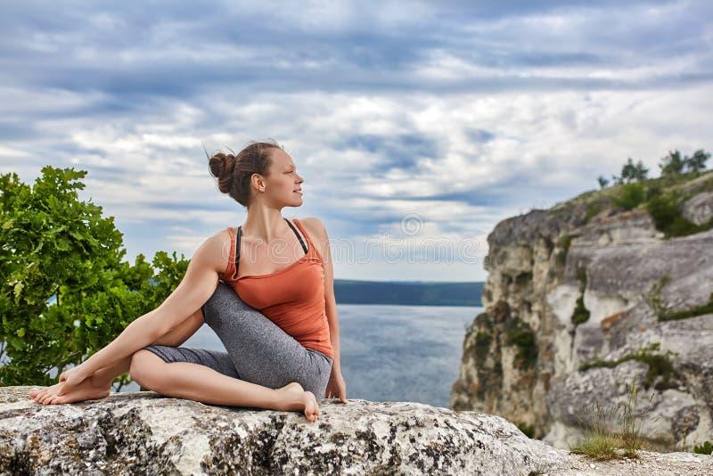 Bella giovane donna che medita nella posa di yoga ad un grande fiume contro il cielo drammatico fotografia stock