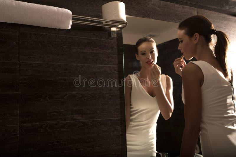 Bella giovane donna che mette sul trucco nel bagno immagine stock