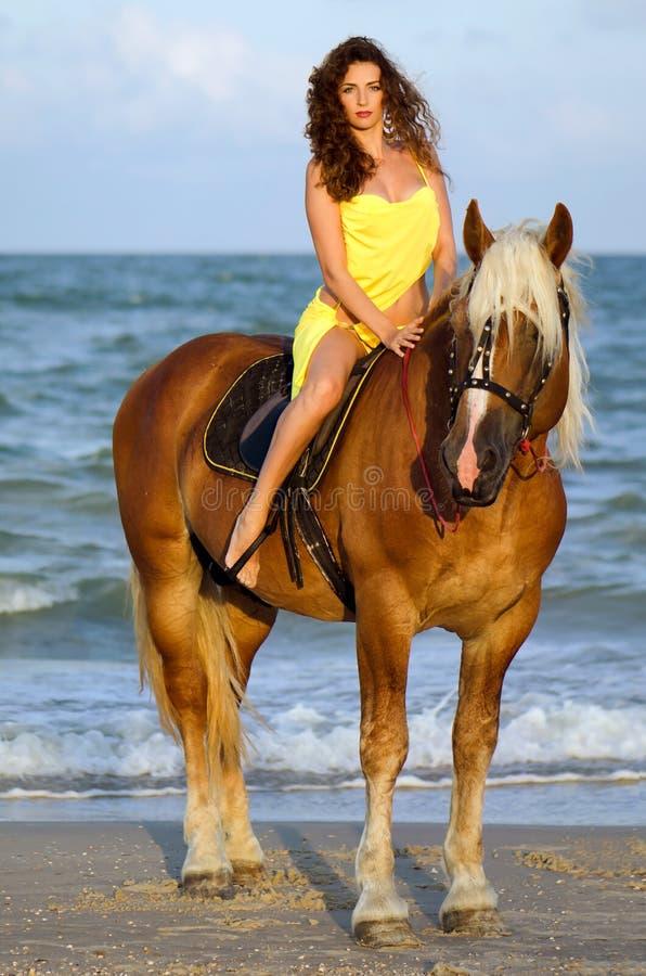 Bella giovane donna che monta un cavallo fotografia stock