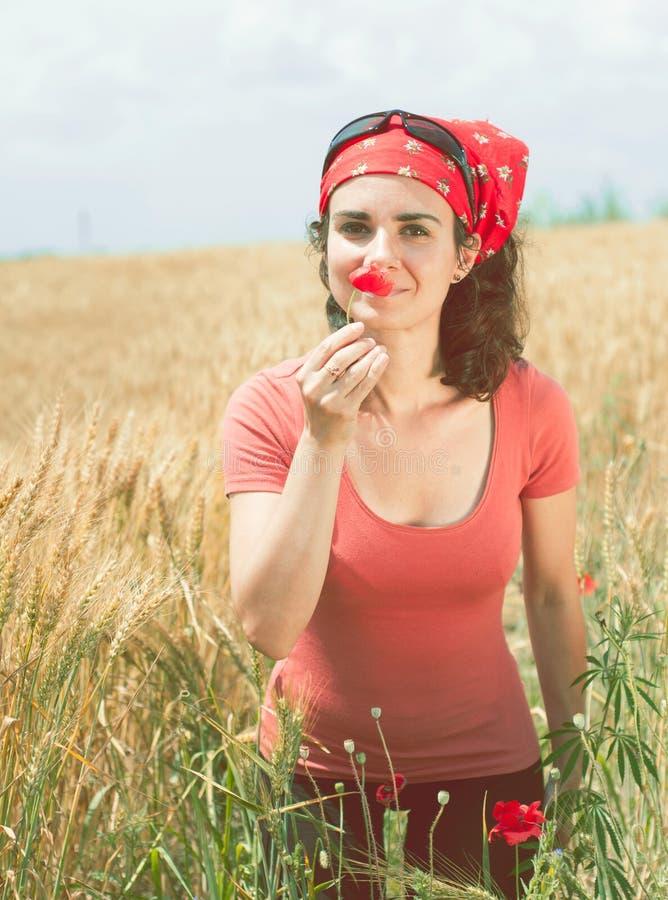 Bella giovane donna che odora un papavero fotografia stock