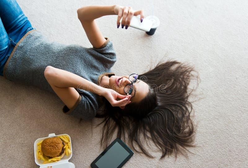 Bella giovane donna che per mezzo di un telefono cellulare fotografia stock libera da diritti