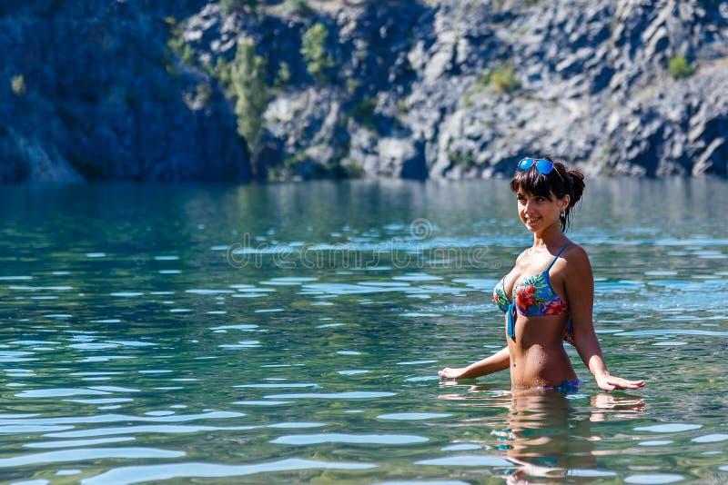 Bella giovane donna che porta un bikini che sta in una La della montagna fotografia stock