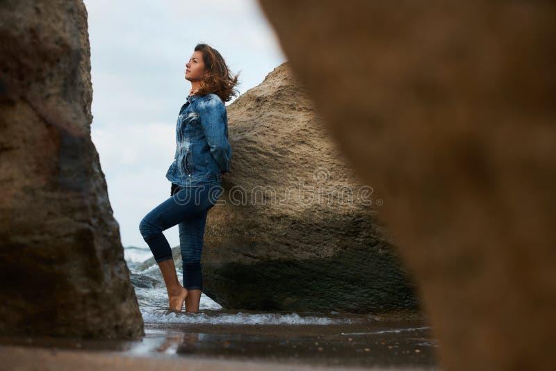 Bella giovane donna che posa fra le rocce immagini stock