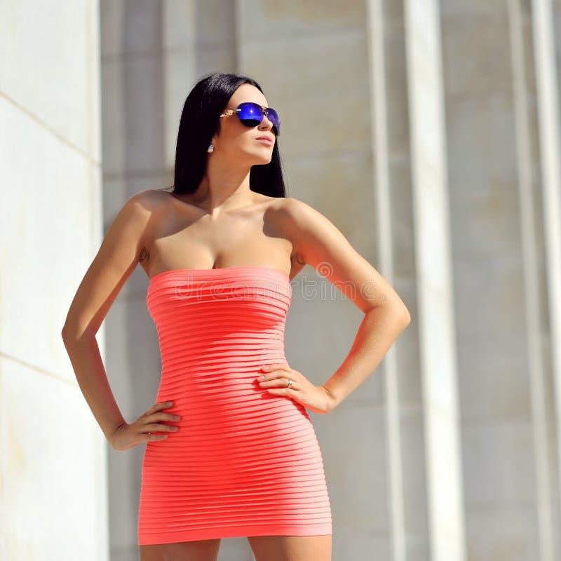 Bella giovane donna che posa gli occhiali da sole d'uso fotografie stock libere da diritti